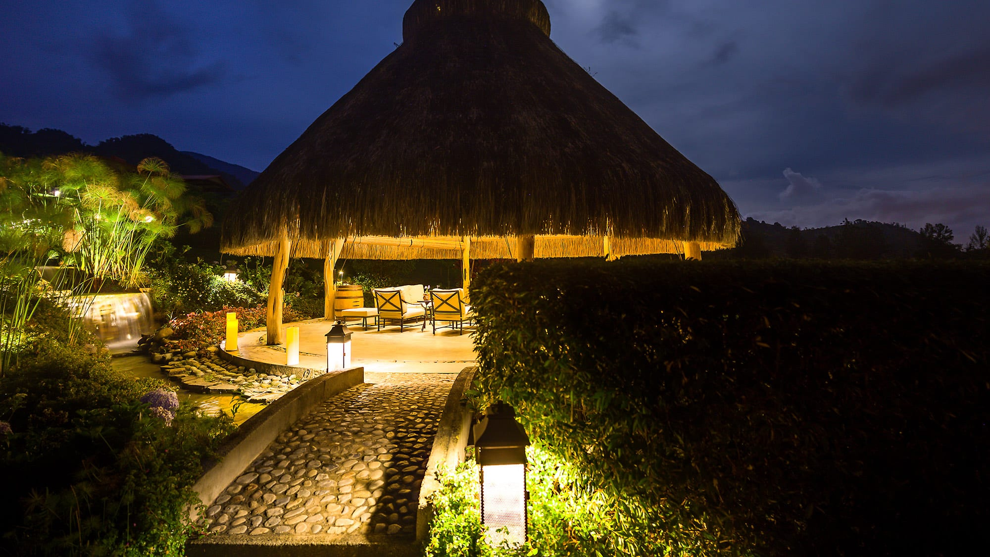 outdoor straw hut illuminated at dusk