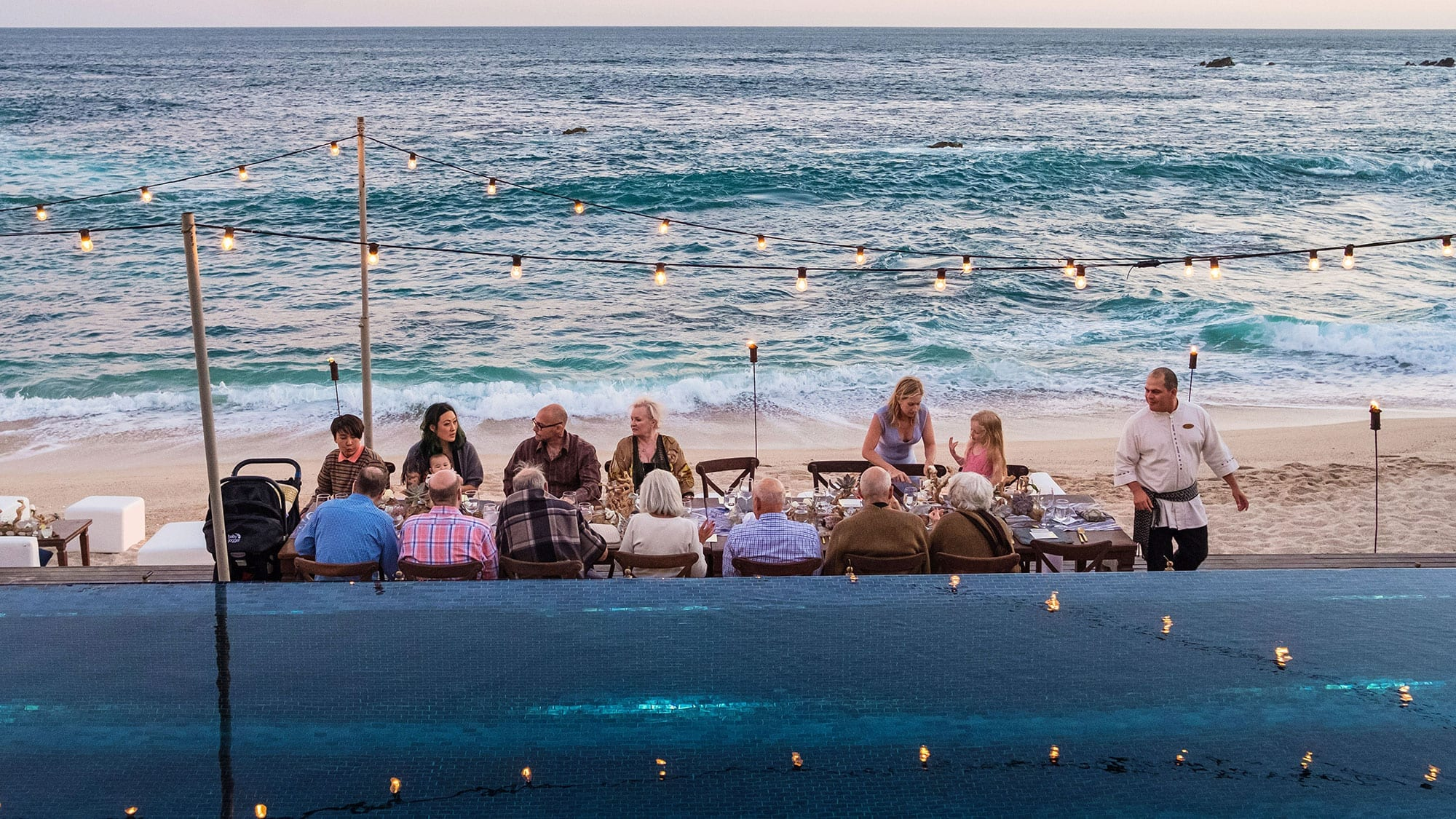 group of people dining on the beach
