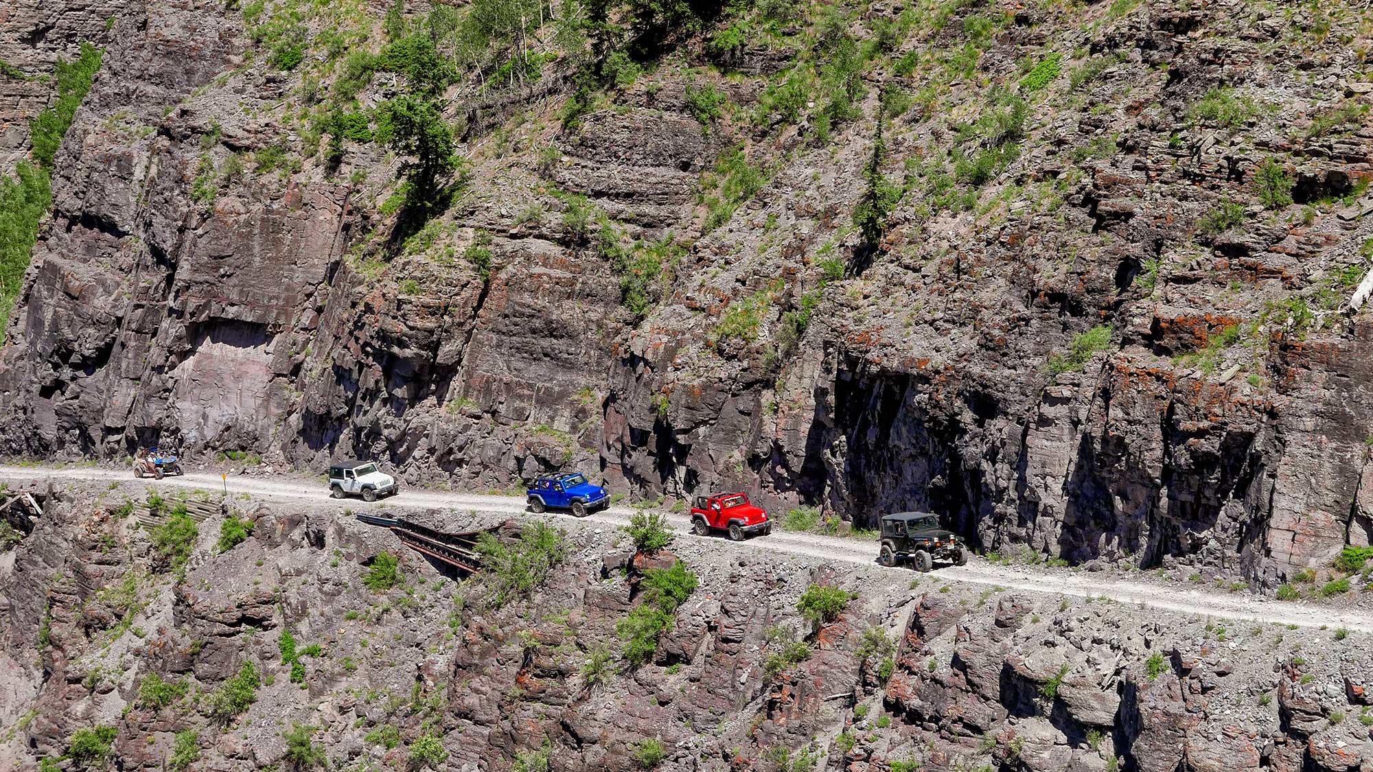 colorful jeeps at edge of cliff