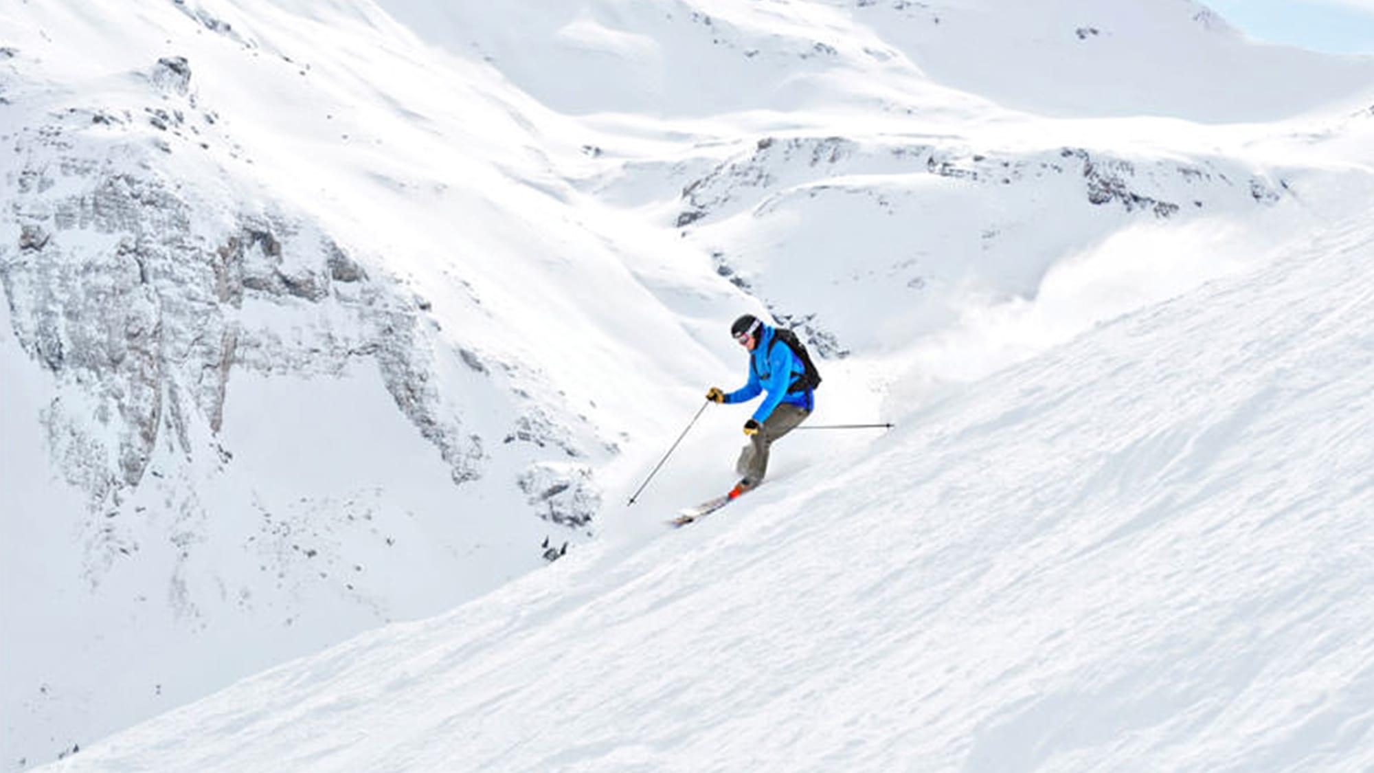 solo skier down steep white mountain
